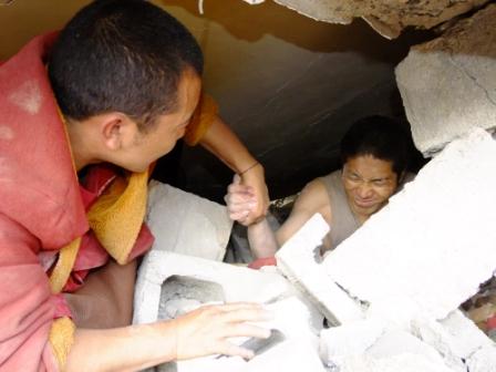 Un monaco tibetano nel momento del salvataggio d'un terremotato a Yushu
