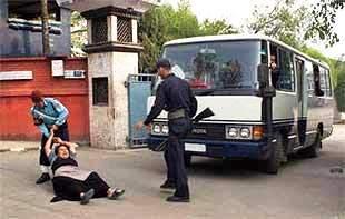 una tibetana cerca di fermare l'autobus sul quale sono caricati i tibetani per essere riportati oltre frontiera