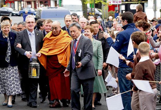 Richard Moore regge con Sua Santità il Dalai Lama la fiamma di Santa Brigida mentre viene accolto il 13 aprile 2011 dai bambini delle scuole di Kildare in Irlanda. Foto / Tenzin Taklha / OHHDL