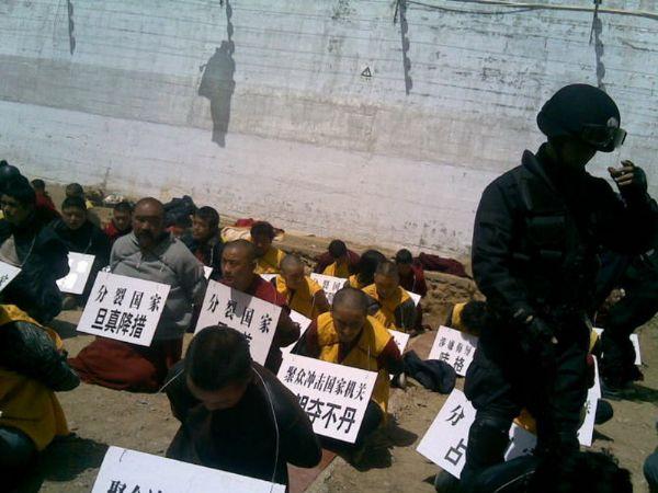 """Monaci ammanettati ed inginocchiati a terra con cartelli al collo col loro nome ed accusa: """"separatista"""" o """"indipendentista""""."""