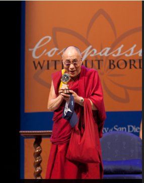 His Holiness the Dalai Lama holding the University of San Diego's Medal of Peace presented to him before his talk in San Diego on 18 April 2012/Photo/Tim Mantoani