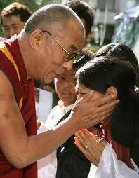 Sua Santità il Dalai lama impartisce la benedizione toccando la testa di una giovane tibetana.