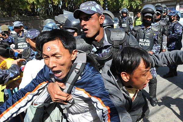 Nepalese riot police arrest Tibetan protesters in front of the consular section of the Chinese Embassy during a protest marking the 53rd anniversary of the 1959 Tibetan uprising against Chinese rule in Kathmandu on March 10, 2012/Prakash Mathema / AFP / Getty Images