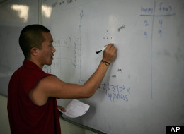 In this June 7, 2012 photo, a Tibetan Buddhist monk tries to solve a mathematical problem on a white board during a class at an educational complex in Sarah, India. Pushed by the Dalai Lama, who has became a fierce proponent of modern schooling, a series of programs were created in exile to teach scientific education to monks, the traditional core of Tibetan culture. (AP Photo/Altaf Qadri)