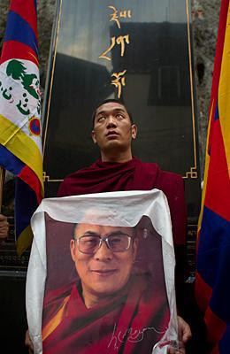 Un monaco tibetano mostra un ritratto del Dalai Lama per ricordare i martiri autoimmolatisi per la causa tibetana.