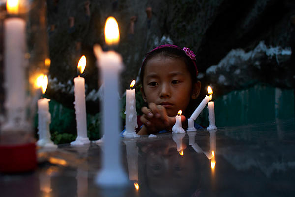 An exile Tibetan girl lights a candle during a candlelit vigil to remember two Tibetans who have self-immolated in Tibet, in Dharmsala, India, Tuesday, 7 August 2012