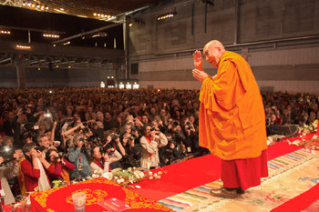 His Holiness the Dalai Lama greeting the audience before the start of his teachings at the Forum Fribourg in Fribourg, Switzerland, on April 13, 2013. Photo/Manuel Bauer