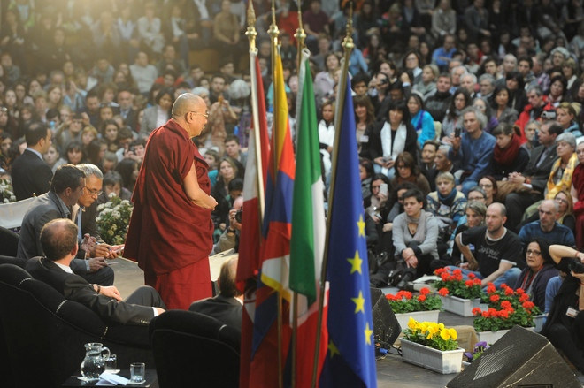 "His Holiness the Dalai Lama during his talk ""Happiness in a Troubled World"" in Palatrento Stadium in Trento, Italy, on April 11, 2013"