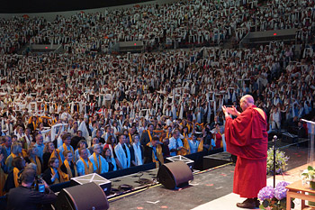 His Holiness the Dalai Lama acknowledging the 11,000 members of the audience wearing white silk scarves at the end of his talk at Veterans Memorial Coliseum in Portland, Oregon on May 11, 2013. Photo/Jeremy Russell/OHHDL