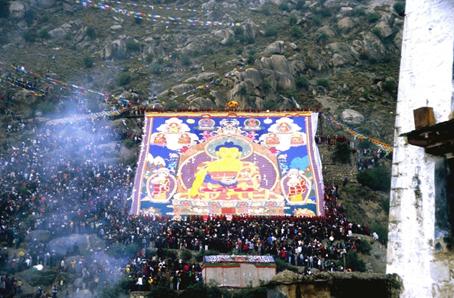 Esibizione di tangka (dipinto votivo su tela) durante celebrazione nel monastero di Drepung