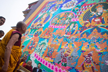 His Holiness the Dalai Lama looking at a huge appliqué thank of Guru Rinpoche hanging from Sera Jey Monastery as he arrives for the fifth day of his teaching in Bylakuppe, Karnataka, India on December 29, 2013. Photo/Tenzin Choejor/OHHDL