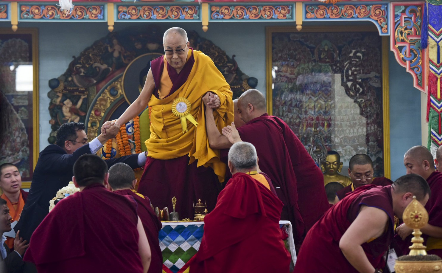 Tibetan spiritual leader the Dalai Lama is assisted by his aides as he prepares to perform rituals during the inauguration of a Mongolian Buddhist temple in Bodh Gaya, India, Jan. 9, 2017. (AP Photo/Manish Bhandari)