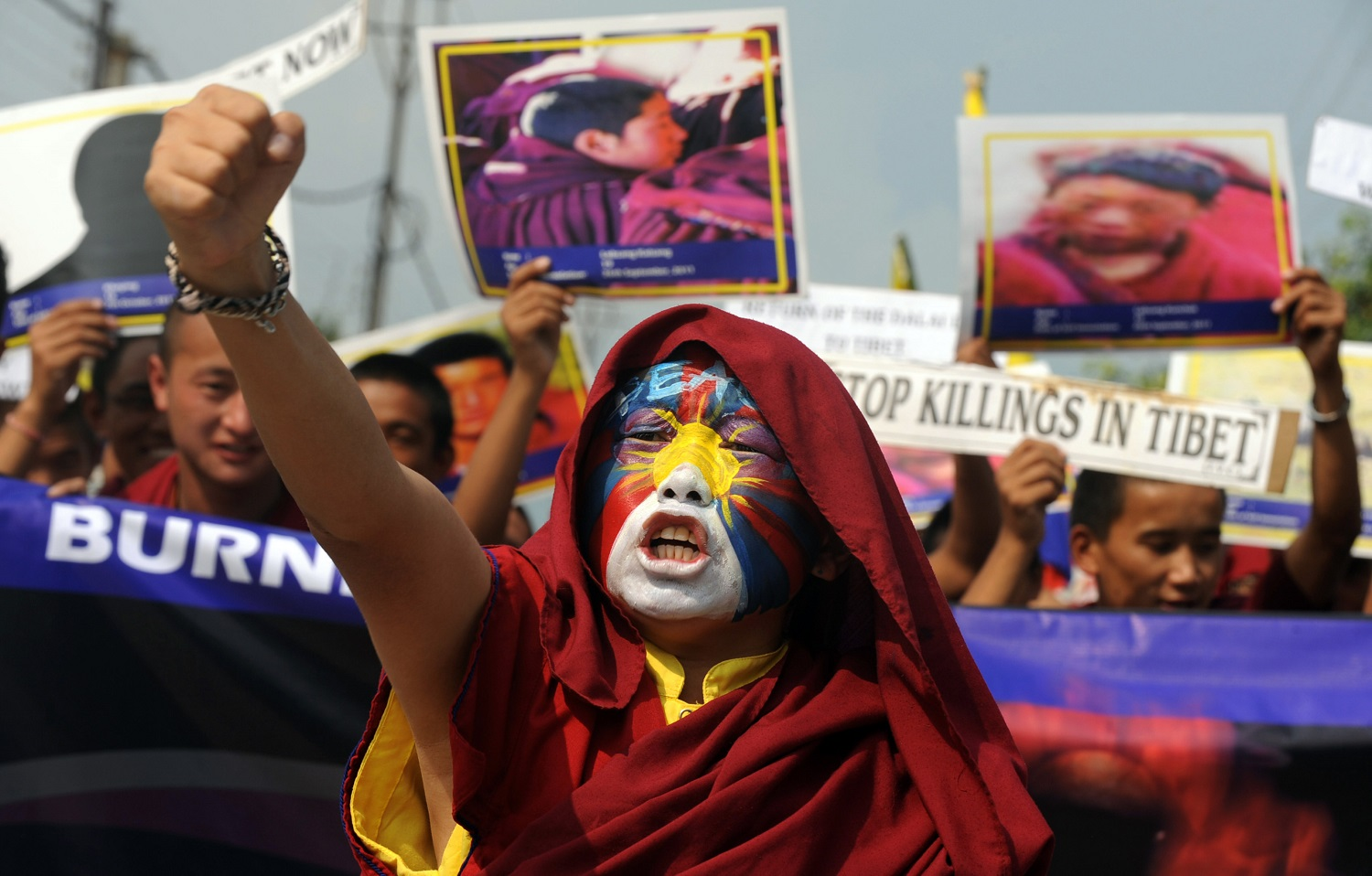 A Buddhist monk with the Tibetan flag painted on his face, in Siliguri, India, November 2011, protests in solidarity with dozens of monks who self-immolated in Tibetan parts of China to draw attention to their opposition to Beijing's repression of indigenous culture.