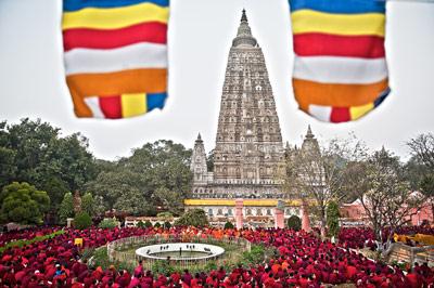 Il gran Stupa della Mahabodhi, dove il Buddha conseguì l'illuminazione, a Bodhgaya tra due bandiere del Dharma.